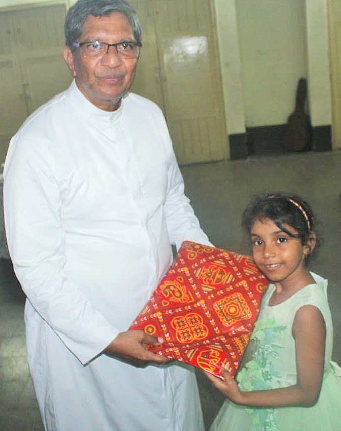 Shanaya Rodrigues receiving a prize at the hands of Parish Priest